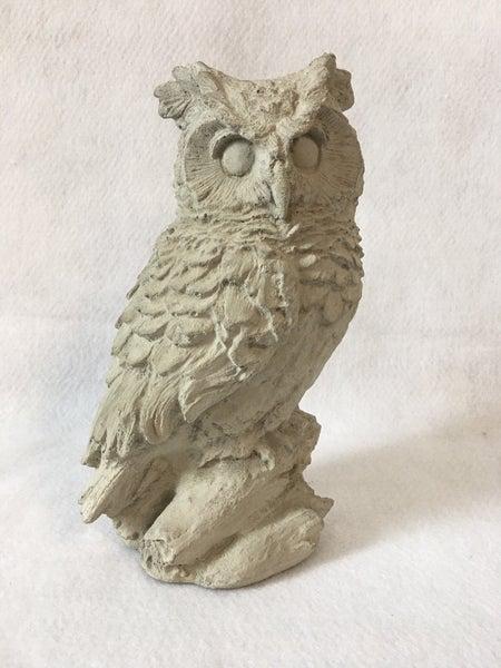 Concrete owl on branch