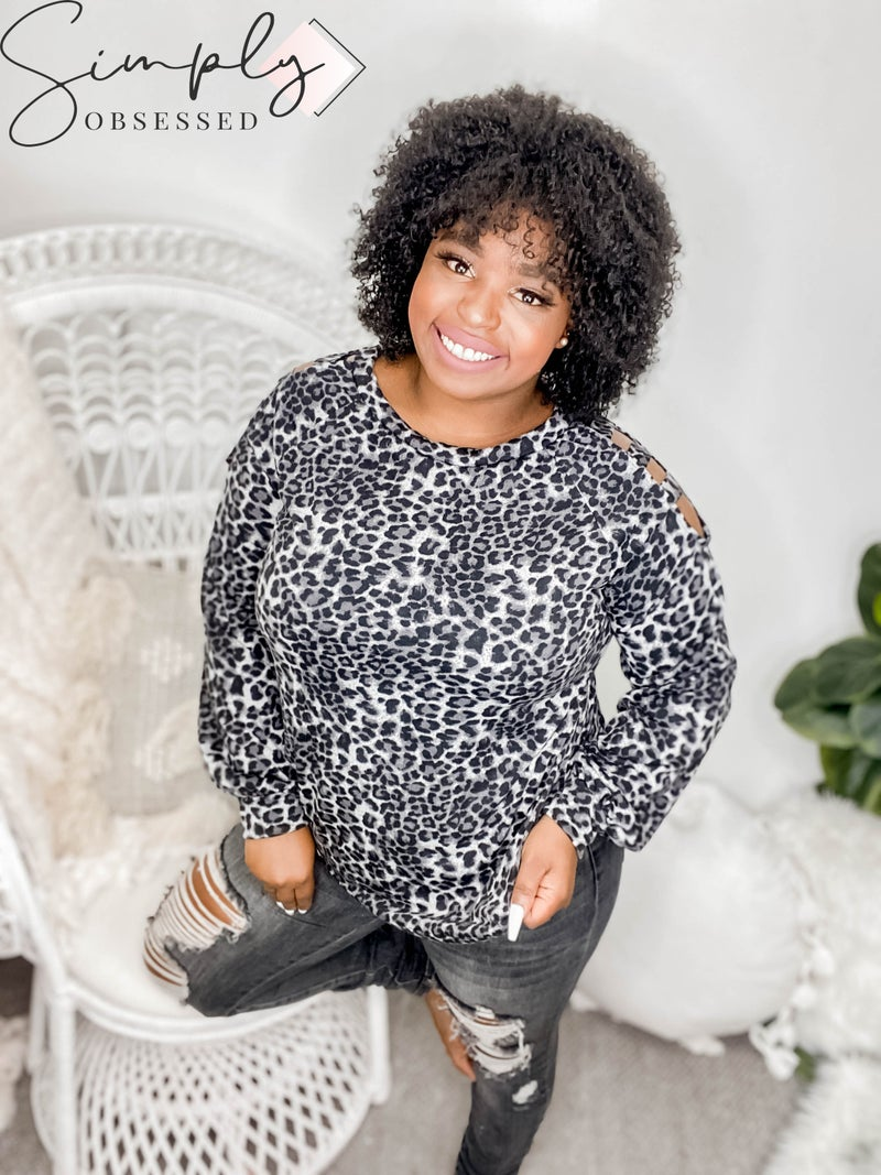 WHITE BIRCH-A long sleeve leopard print knit top with a round neck featuring a cutout detail and a loose fit