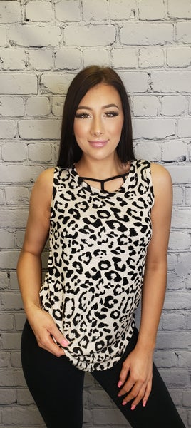 White Birch - Sleeveless cheetah print knit top with round neck featuring a high low hemline