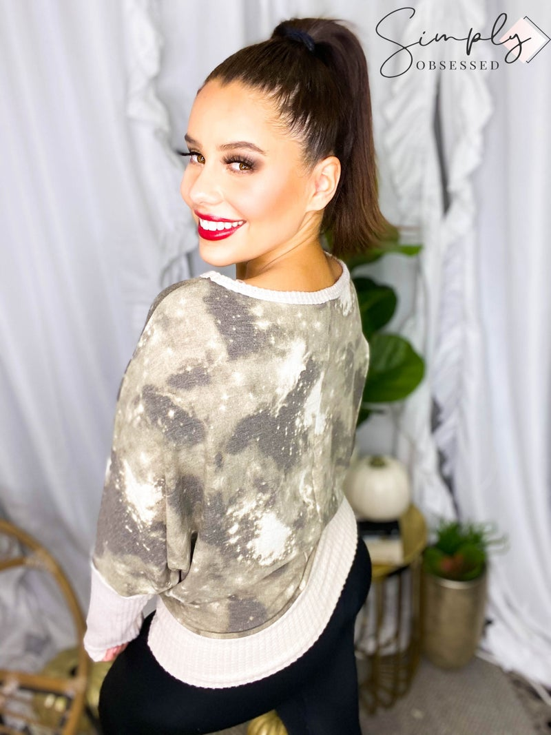 WHITE BIRCH-A long sleeve tie dye knit top with a v-neck featuring a solid trim detail and dolman sleeves.