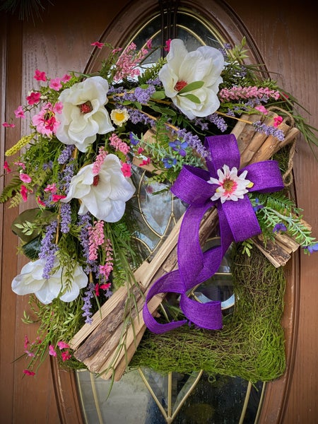 Cross with spring flowers and purple bow
